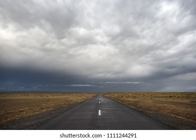 Empty asphalt road under stormy dramatic sky. Copy space for text or product