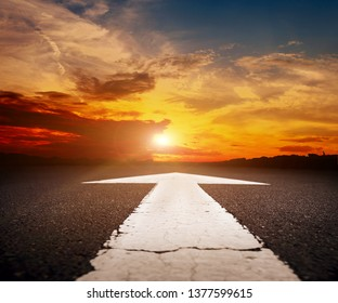 An empty asphalt road with the white arrow at sunset