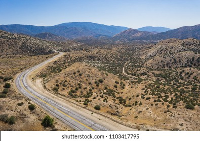 Empty asphalt road winds into the mountains of the Angeles National Forest in the Mojave Desert.