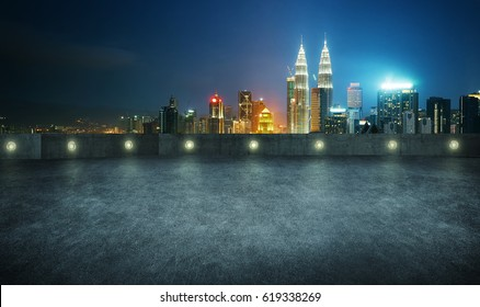 Empty asphalt roof top with modern city skyline , night scene ,Kuala Lumpur , Malaysia .
