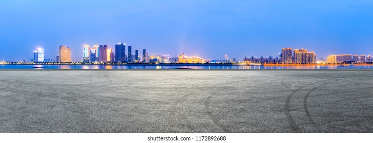 Empty asphalt square and modern buildings in Hangzhou at night