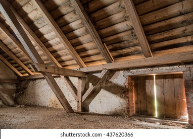Empty attic of an old house with a closed window