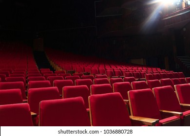 Empty auditorium. Theatre. Red chair. Light of spotlights.
