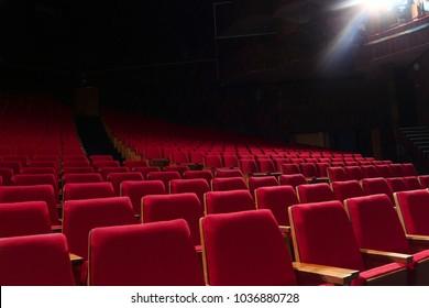 Empty auditorium. Theatre. Red chair. Light of spotlights.
