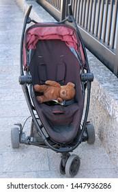 Empty baby stroller with teddy bear toy inside