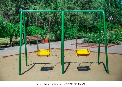 empty baby yellow swing stand in the Park