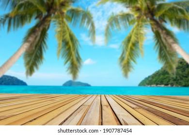 El foco selectivo en la mesa vacía de bambú representa el producto de exposición o montaje con el agua desenfocada del mar y el fondo de la isla tropical. Mar turquesa y cielo azul con dos cocoteros.