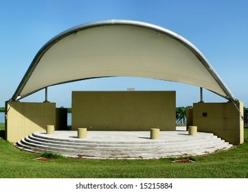 Empty bandshell outdoor amphitheater on a sunny day. There is a cloudless, blue sky behind the structure, and a grassy lawn in front of curved steps. Copy space in horizontal composition.