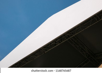 Empty banner with copy space on roof of open-air stage against blue sky