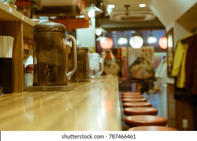 An empty bar with jugs of water inside a popular ramen shop in Shinjuku, Tokyo, Japan. A ramen shop is a restaurant that specializes in ramen dishes, the wheat-flour Japanese noodles in broth.
