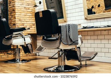 Empty barbershop with armchairs, barber equipment and mirrors on walls