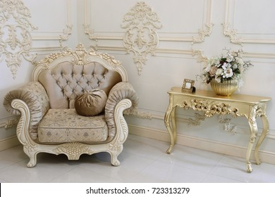 Empty baroque studio with armchair and small gilt table and molding on walls