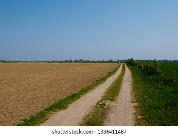 empty barren field in front of a blue sky with a footpath leading to the horizon