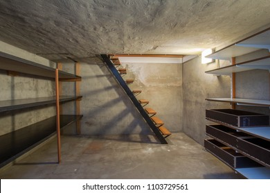empty basement in abandoned old industrial building with little light and a wooden stairs