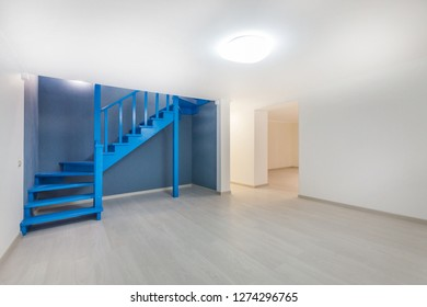 Empty basement room with laminate flooring, high ceiling and deep blue wooden staircase