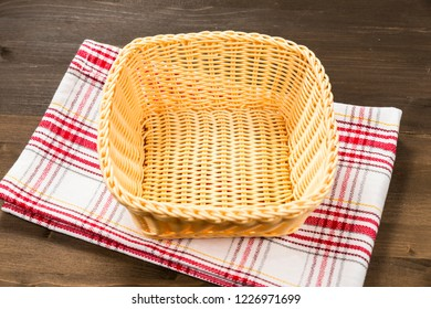 Empty basket with checkered tablecloth on a wooden background