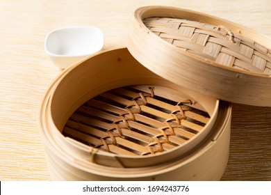 Empty basket of dim sum made by bamboo material and chopsticks. Chinese Traditional cuisine concept. Dumplings Dim Sum in bamboo steamer with text copy space. Asian food background