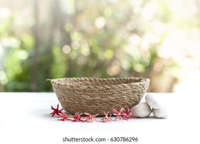 Empty basket and lovely flower on wooden table and soft light background.