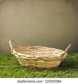 Empty basket on grass over grunge background