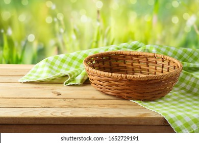 Empty basket with tablecloth on wooden table over green bokeh background. Spring and easter mock up for design.