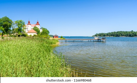 An empty bathing pier in lake Vanern with reedbed in the foreground and Lacko castle in the background. Location Lacko outside Lidkoping in Sweden.