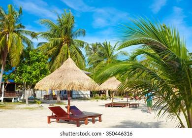 Empty beach bed under thatched umbrellas on a sandy beach
