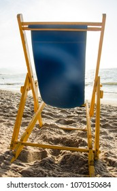 Empty beach chair in the sand.