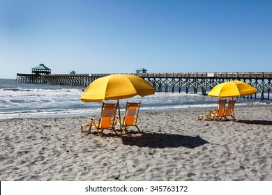 Empty beach chairs on the sand near Folly Beach pier outside Charleston, South Carolina seem to invite vacationers to come and relax.