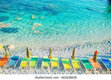 Empty beach with closed umbrellas on italian coast