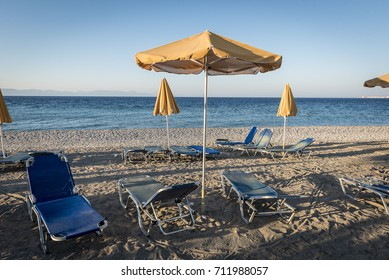 empty beach with deckchairs and a yellow parasol