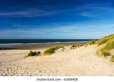 Empty beach with dunes waves and the sea