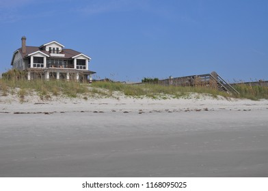 Empty beach with dunes and wooden walkway to the beach.