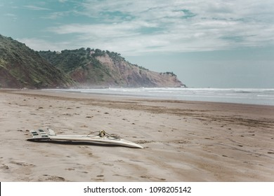 Empty beach with no people and one surfboard left on the sand in low season in Ayampe, a surf town on the west coast of Ecuador