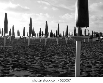 Empty beach, parasols  at the sunset at the end of a season