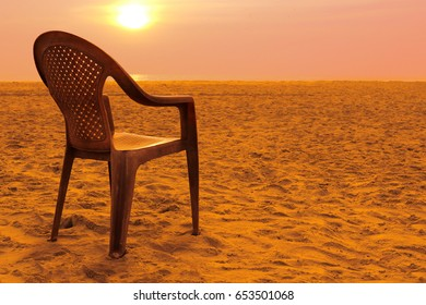 Empty beach and a plastic chair in the rays of a hot setting sun.