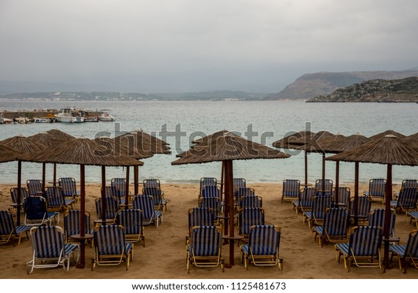 Empty beach. Sunbeds and umbrellas on a cloudy day. After season. Bad weather in Kato Marathi, Marathi Bay, Crete, Greece. Rows of white and blue empty sunbeds and  umbrellas on a gold sand beach.
