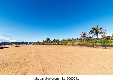 Empty beach with tire tracks against blue sky at Addinton Beach in Durban, South Africa