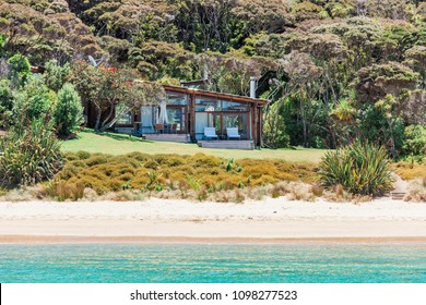 Empty beach with trees and buildings in Bay of Islands, New Zealand