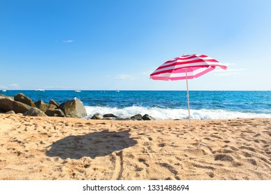 Empty beach with waves, sea and striped pink parasol
