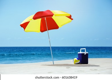 Empty beach without people with umbrella and accesorries at sea background
