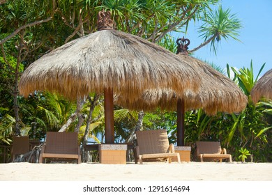 empty beautiful idyllic beach background with recliners, chairs, exotic straw tents, palm trees and bright blue sky