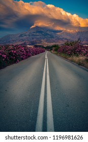 Empty beautiful and scenic road surrounded by big beautiful oleander flowers with the Saos mountain peak in the background with a big cloud formation on Samothrace Island in Greece