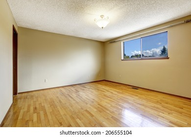 Empty bedroom in soft ivory with one window and hardwood floor