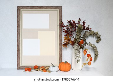 Empty beige frame with pumpkins and autumnal bouquet