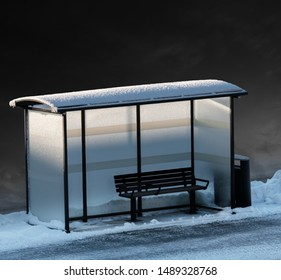 Empty bench in bus stop in winter, with dark sky in background and some dim light from low sun.