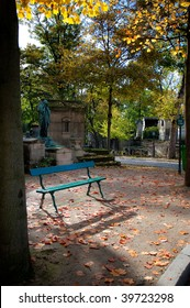 Empty bench in a cemetery surrounded by beautiful autumn leaves. Location is world-famous Pere Lachaise cemetery in Paris, France.