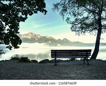Empty bench at the lake beach. Magnificent lake in South Bavaria, Germany.  The concept of walking and eco-tourism. Water reflects the surrounding mountains and forest