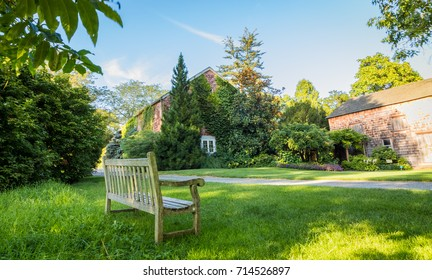 An empty bench opens to ivy covered buildings and beautiful landscape on a late summer day