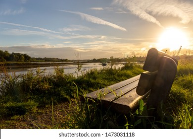 An empty bench over looking a peaceful and idyllic river scene in the heart of the Suffolk countryside