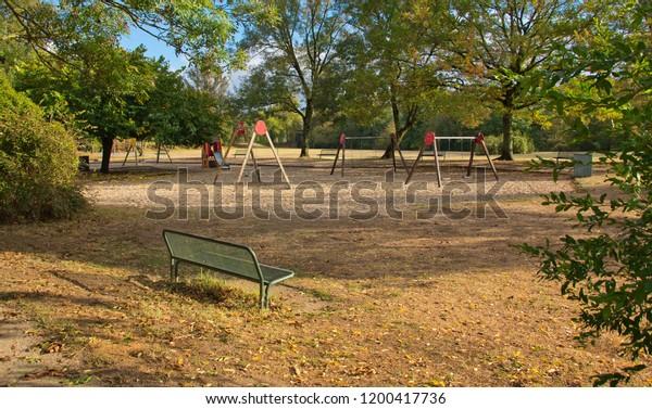 Empty bench overlooking empty playground